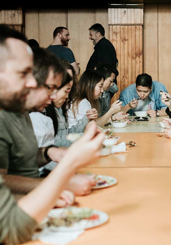 People gathered around long tables eating lunch at CityLight Church North Adelaide.